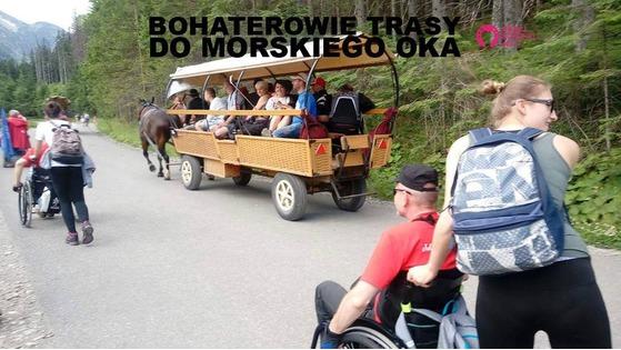 Zdjęcie przedstawia dwie osoby pokonujące trasę do Morskiego Oka na wózkach inwalidzkich. W tle wóz z pełnosprawnymi turystami.