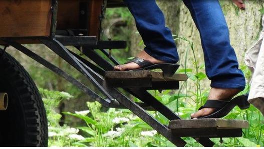 Zdjęcie przedstawia osobę w klapkach wchodzącą po stromych schodach na wóz ciągnięty przez konie, którym turyści jadą na Morskie Oko